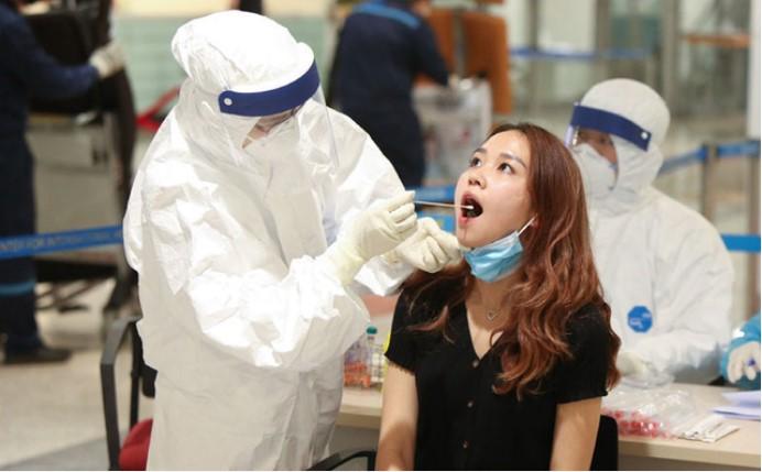 Đội ngũ y bác sĩ lấy mẫu xét nghiệm Covid-19 cho hành khách đi về từ vùng dịch. (Ảnh qua kinhtedothi)