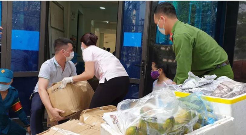 Lực lượng chức năng vận chuyển nhu yếu phẩm vào khu vực cách ly ở Trúc Bạch, Ba Đình, Hà Nội. (Ảnh qua giadinh)