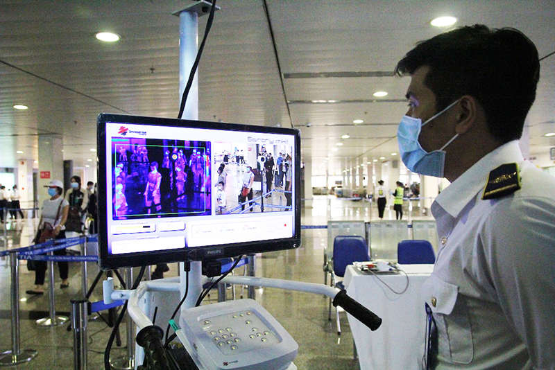 Hành khách qua chốt kiểm soát virus corona tại sân bay Tân Sơn Nhất. (Ảnh qua dantri)