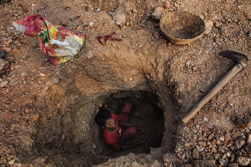 Một cậu bé đang đào Mica dưới hầm mỏ, mà không hề có bất kỳ đồ bảo hộ nào.