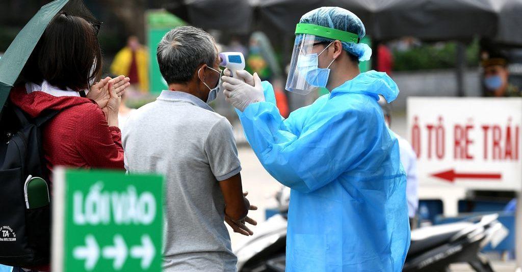 Nhân viên y tế mặc trang phục bảo hộ, đang kiểm tra nhiệt độ cho khách tại bệnh viện Bạch Mai ở Hà Nội, ngày 24/3. (Ảnh qua news)