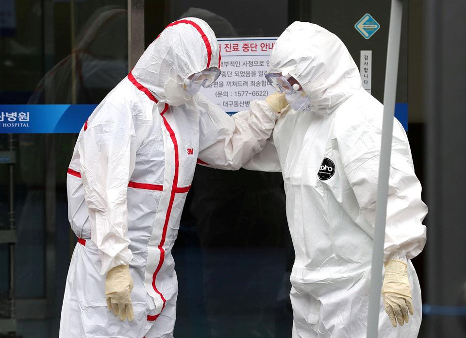 Các nhân viên y tế mang đồ bảo hộ động viên nhau bên ngoài một bệnh viện ở tâm dịch Daegu, Hàn Quốc hôm 28/2. (Ảnh qua tuoitre)