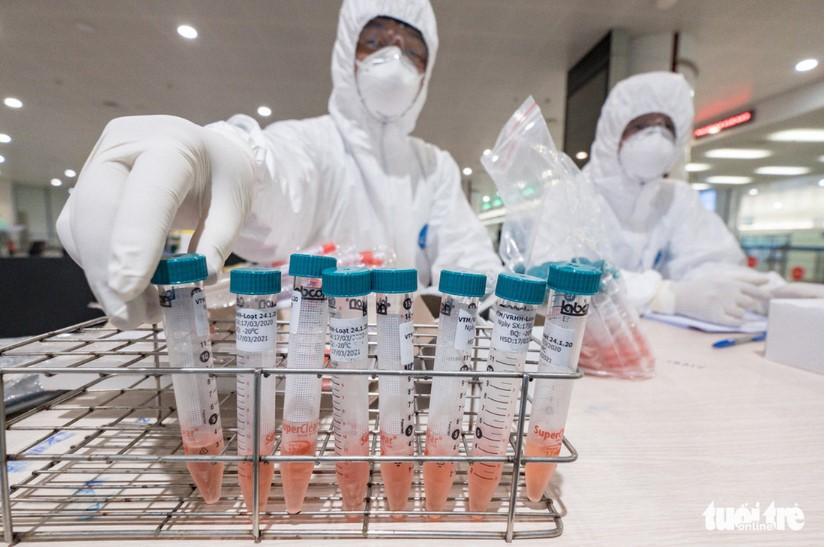 Nhân viên y tế chuẩn bị những ống nghiệm chứa dung dịch để lấy dịch họng, dịch mũi cho hành khách tại sân bay Nội Bài. (Ảnh qua tuoitre)
