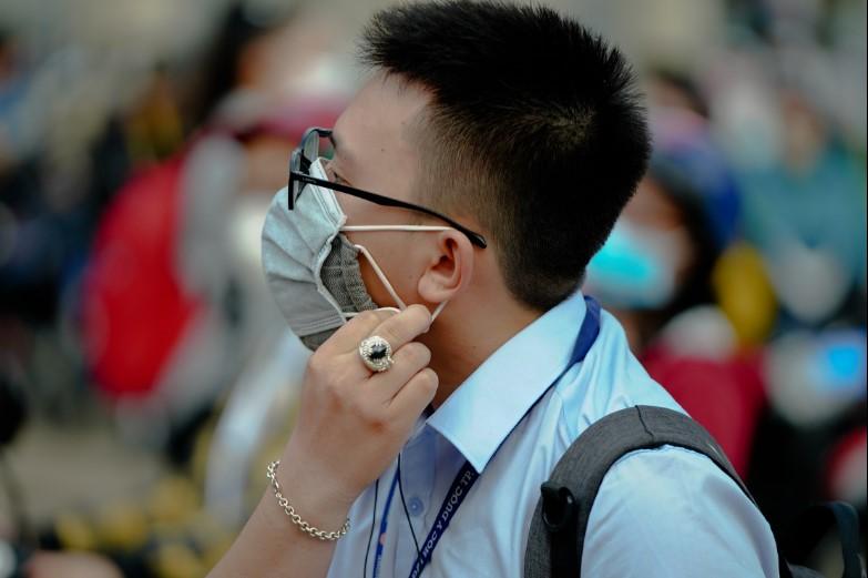 Sinh viên Đại học Y dược TP.HCM cẩn thận đeo hai khẩu trang khi trở lại trường sáng nay, 9/3. (Ảnh qua dantri)