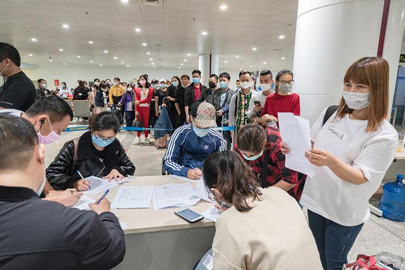 Hành khách đến từ các chuyến bay quốc tế thực hiện khai báo y tế tại sân bay Nội Bài trong ngày 18/3. (Ảnh qua tuoitre)
