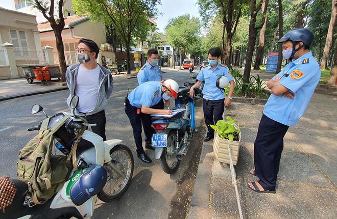Lực lượng chức năng ở TP.HCM xử phạt người không đeo khẩu trang khi ra nơi công cộng. (Ảnh qua thanhnien)
