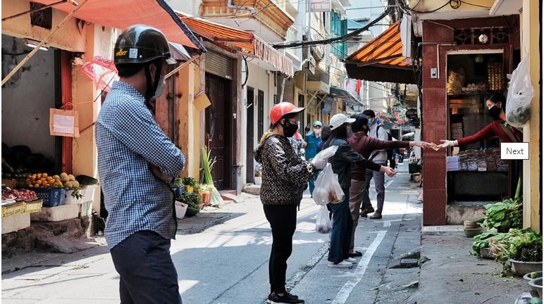Người dân đứng cách 2m, chờ đến lượt mua hàng tại phố Yên Thái, Q. Hoàn Kiếm, Hà Nội sáng 14/4. (Ảnh qua tuoitre)