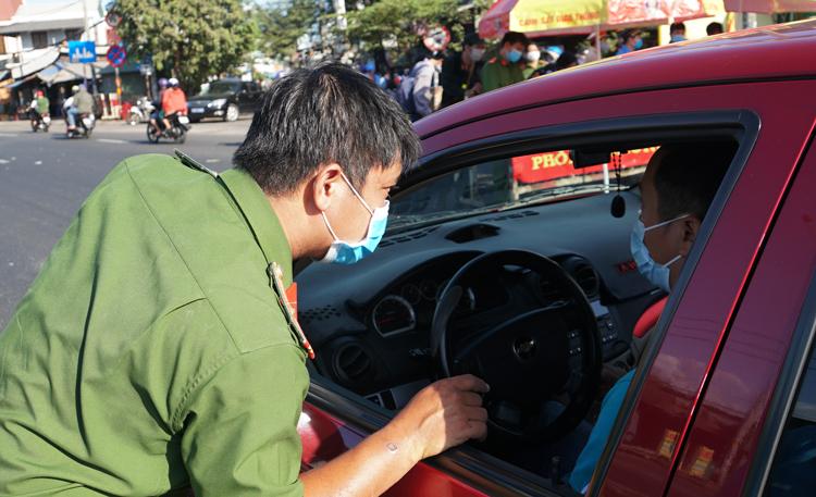 Công an quận Thủ Đức kiểm tra ôtô vào thành phố, nhắc nhở người dân đeo khẩu trang tại cầu Vĩnh Bình (cửa ngõ TP.HCM - Bình Dương). (Ảnh qua vnexpress)