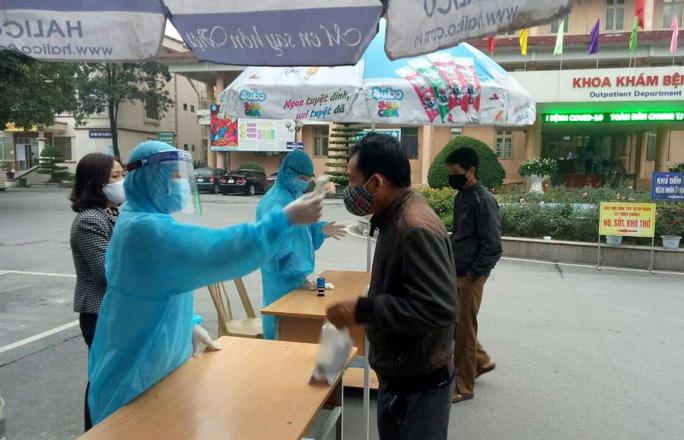 Bác sĩ Bệnh viện Đa khoa tỉnh Hà Nam kiểm tra y tế, đo thân nhiệt những người ra vào bệnh viện. (Ảnh qua nld)