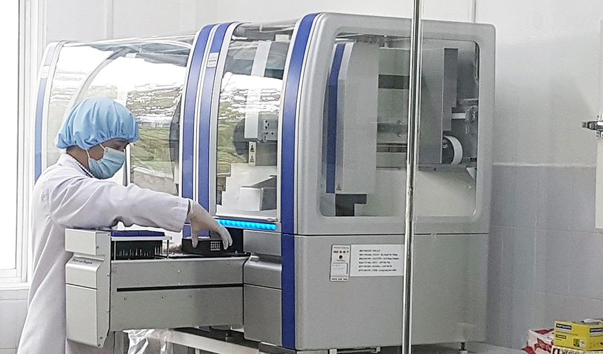 Kỹ thuật viên của CDC Quảng Nam thực hiện xét nghiệm trên hệ thống xét nghiệm Realtime PCR. (Ảnh qua tuoitre)
