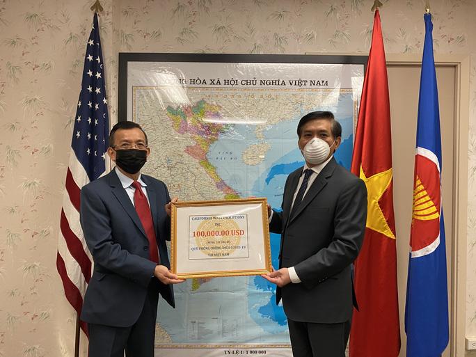 Ông David Dương (trái), Chủ tịch Công ty California Waste Solutions có trụ sở tại Bắc California, Mỹ trao số tiền ủng hộ. (Ảnh qua nld)