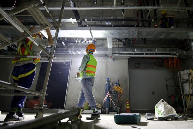 Phía dưới, tại tầng hầm B2, các công nhân vẫn đang miệt mài lắp các thiết bị cơ điện, đóng trần. (Ảnh qua thanhnien)