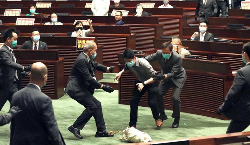 Nhân viên an ninh ngăn cản nghị sĩ Ted Hui Chi-fung khi ông cố ném túi đựng rau củ thối về hướng chủ tịch Hội đồng Lập pháp Hong Kong Andrew Leung ngày 28-5.
