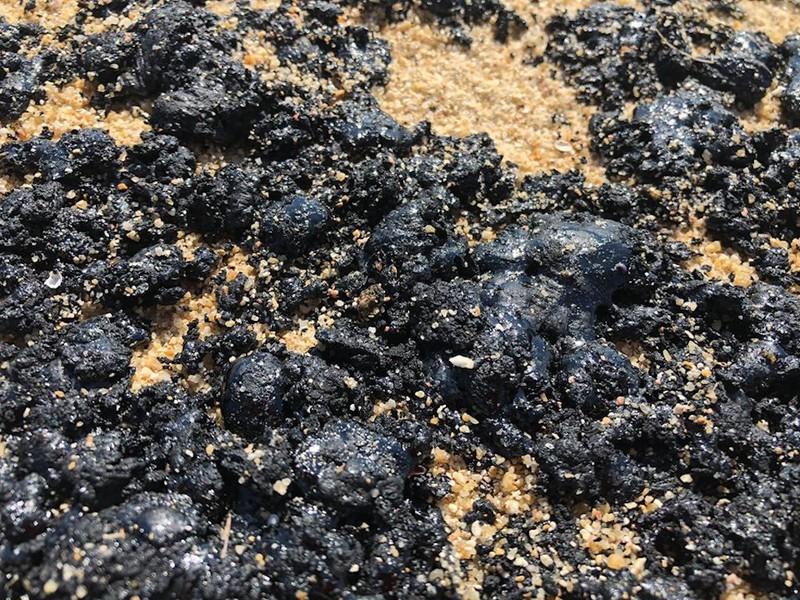 Chất thải màu đen dọc bờ biển Quảng Ngãi tan chảy, vón cục. (Ảnh qua Zing)