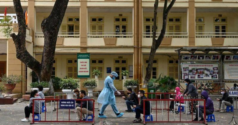 Người dân đeo khẩu trang thực hiện giữ khoảng cách an toàn trong khi chờ xét nghiệm nhanh tại một địa điểm gần bệnh viện Bạch Mai hôm 31/3/2020. (Ảnh qua ntdvn)