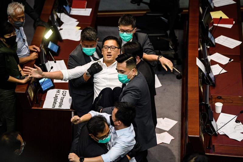 Chính trị gia phe dân chủ, ông Lam Cheuk-ting bị nhân viên an ninh trục xuất sau khi ném những mẩu giấy xé từ tài liệu quy tắc của Hội đồng lập pháp Hồng Kông, trong một cuộc xô xát giữa những nhà lập pháp ủng hộ dân chủ và ủng hộ Bắc Kinh tại buổi bỏ phiếu ghế chủ tịch tại trụ sở Hội đồng lập pháp Hồng Kông vào ngày 18/5/2020.