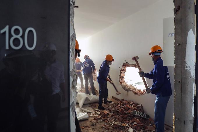 Lực lượng cưỡng chế phá tường ngăn giữa các căn hộ tầng 18 nhà 8B Lê Trực. (Ảnh qua vnexpress)