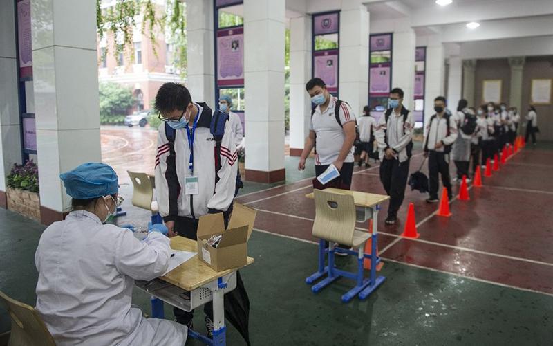 Học sinh xếp hàng chờ lấy mẫu sinh phẩm tại một trường học ở Vũ Hán hôm 14/5.