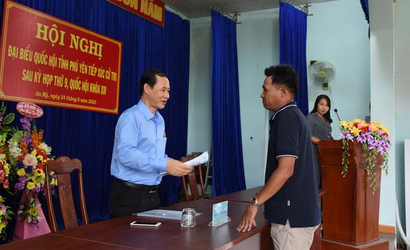 Đại biểu Quốc hội Nguyễn Thái Học - phó trưởng Ban Nội chính trung ương - nhận đơn phản ánh của người dân tại cuộc tiếp xúc cử tri ở huyện Tuy An (Phú Yên). (Ảnh qua tuoitre)