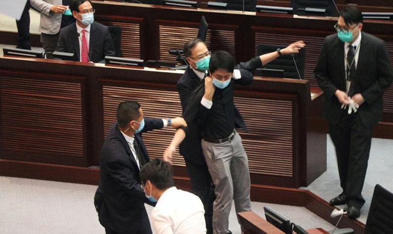 Một nghị viên đối lập gây náo loạn tại cuộc họp của Hội đồng Lập pháp Hồng Kông bị các nhân viên an ninh khống chế áp giải ra ngoài ngày 4.6