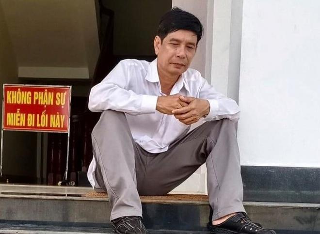 Ông Phước ngồi tại sân tòa trước lúc tuyên án sáng 29/5. (Ảnh qua Zing)
