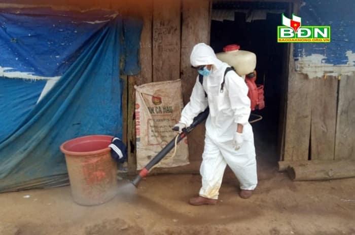 Nhân viên y tế phun hóa chất khử trùng toàn bộ nhà dân tại cụm dân cư số 2. (Ảnh qua baodaknong)
