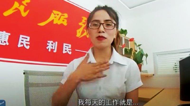 Trong video là một cô gái trẻ ngồi sau bàn làm việc, phía sau phông nền có thể thấy rõ khẩu hiệu tuyên truyền.