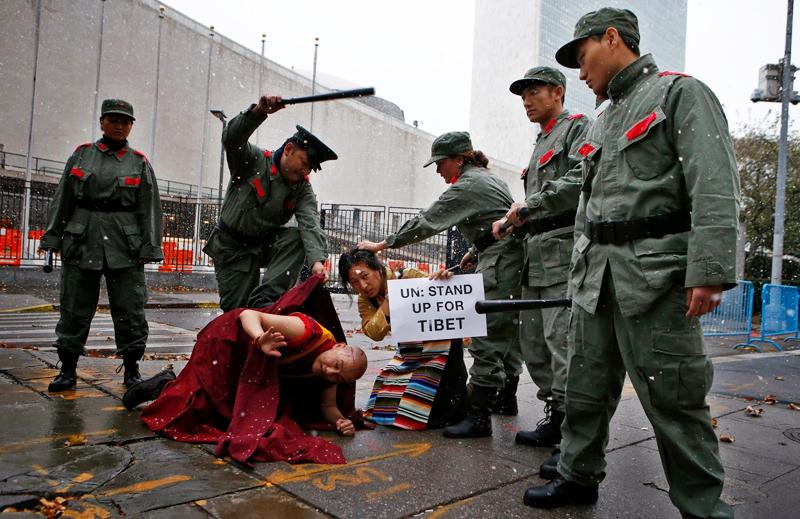 Các diễn viên trình diễn hoạt cảnh lính TQ đánh đập người Tây Tạng trước trụ sở LHQ ở New York ngày 12/11/2013.