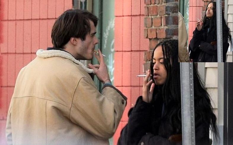 Malia và Rory hút thuốc và trò chuyện cùng nhau hần cửa hàng bánh mỳ Sanwich gần khuôn viên trường Harvard