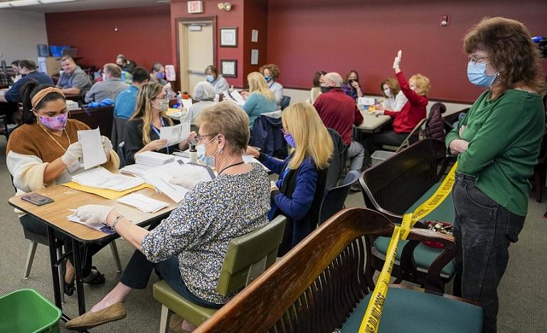 Một giám sát viên của Đảng Dân chủ đang dõi nhân viên kiểm phiếu phân loại và đếm các lá phiếu của Quận Luzerne tại Wilkes-Barre, Pennsylvania vào ngày 4/11/2020