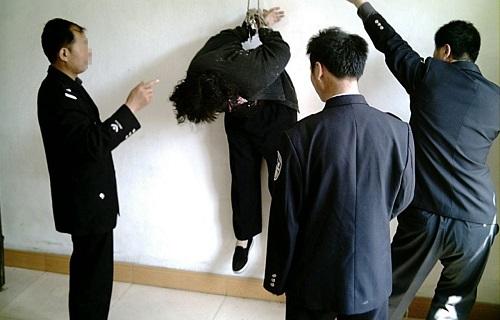 Tái hiện cảnh học viên Pháp Luân Công ở Trung Quốc bị tra tấn.