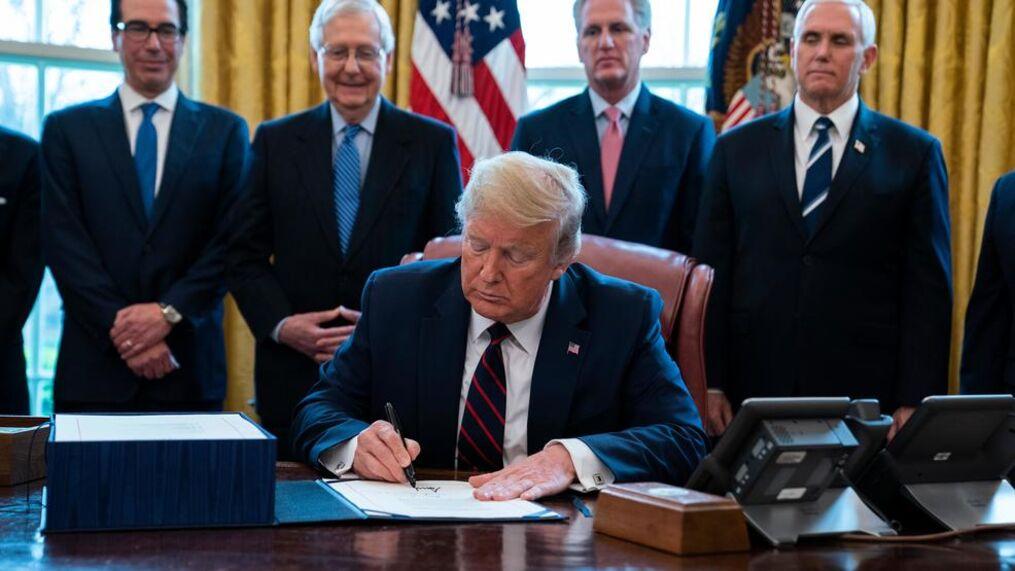 Tổng thống Trump ký gói cứu trợ COVID-19 trong Phòng Bầu dục tại Nhà Trắng (Washington), vào ngày 27/3/2020, với sự theo dõi của Bộ trưởng Tài chính Steven Mnuchin, Lãnh đạo Đa số Thượng viện Mitch McConnell, Lãnh đạo thiểu số Hạ viện Kevin McCarthy, và Phó Tổng thống Mike Pence