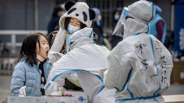 Một bệnh nhi Trung Quốc được nhân viên y tế mặc quần áo bảo hộ lau người khi xét nghiệm axit nucleic COVID-19 trong khuôn khổ chiến dịch xét nghiệm hàng loạt ở quận Đông Thành, Bắc Kinh vào ngày 23/1/2021