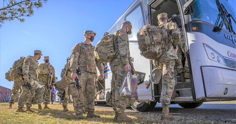Các binh sĩ Lục quân Hoa Kỳ từ Lực lượng Vệ binh Quốc gia của Quân đội New Jersey lên xe buýt tại căn cứ vũ trang Vệ binh Quốc gia ở Blackwood, NJ, ngày 9/1/2021