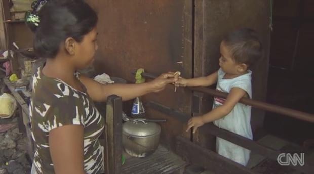 Chị Morena Sumanda đưa thức ăn cho con.