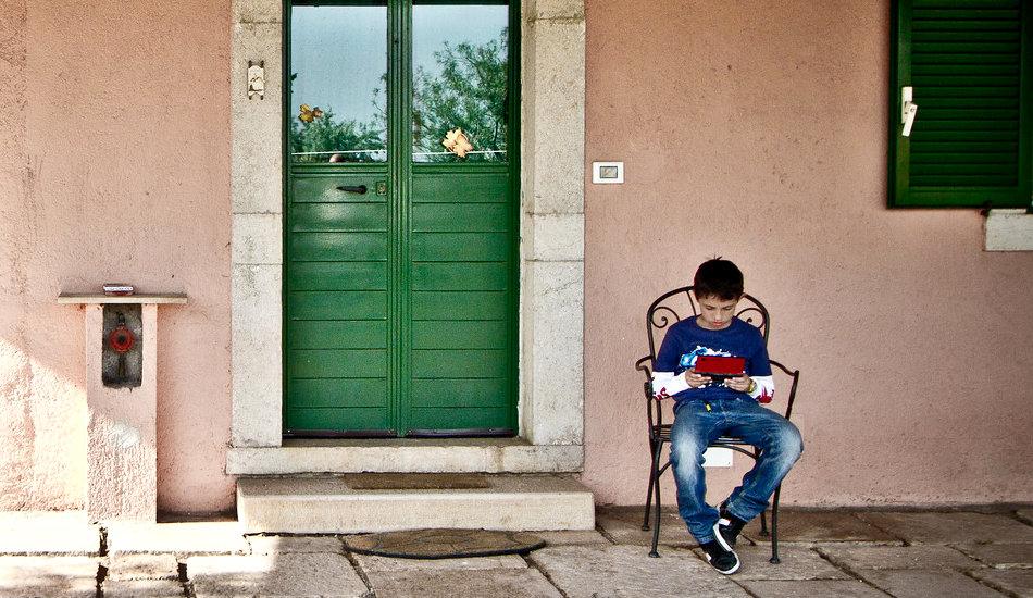Một cậu bé ngồi bên ngoài chơi trò chơi điện tử.