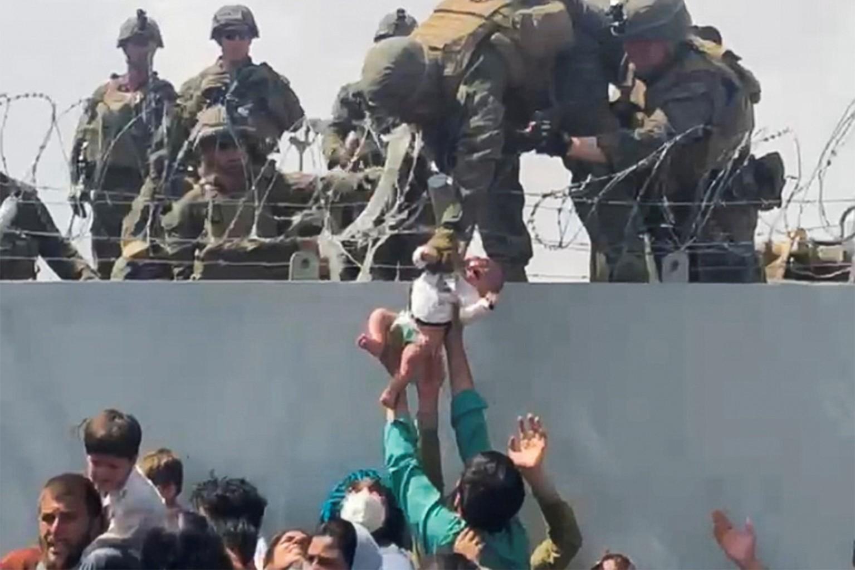 Em bé Afghanistan được đưa qua tường rào thép gai. (Ảnh cắt từ clip)